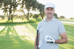 Handsome golfer standing with golf ball Stock Photo