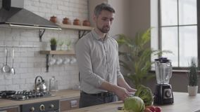 Handsome good-looking man in the shirt cooking dinner checking recipe on the tablet in the kitchen at home. Concept of. Healthy food, home cooking. The guy stock footage
