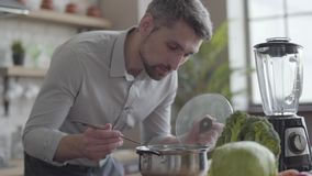 Handsome good-looking man in the shirt cooking soup in the kitchen. Concept of healthy food, home cooking. The guy. A handsome good-looking man in shirt cooking stock video footage
