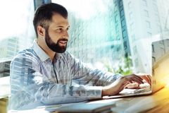 Handsome good-looking man sitting and using laptop. Lowe my job. Handsome joyful good-looking man sitting by the table using the laptop and delighting with his Royalty Free Stock Photo