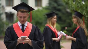 Handsome graduate in mantle typing messages on smartphone, checking job offers. Stock footage stock footage