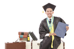 Handsome graduated student sitting and holding certificate. Portrait of handsome graduated student sitting and holding certificate isolated on white background Stock Photos