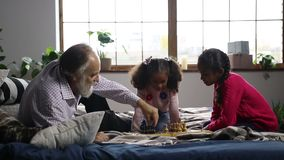 Elderly man playing chess with cute granddaughter. Handsome grandfather with beard playing chess with cute mixed race granddauhter on bed at home. Positive stock video footage