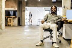 Handsome graphics designer sitting at a desk Stock Image
