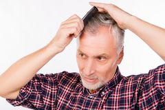 Free Handsome Gray Aged Man Combing Hair Royalty Free Stock Images - 166373609