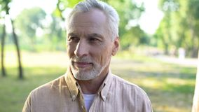 Handsome gray-haired man enjoying weekend in park, happy male pensioner outdoor royalty free stock images