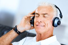 Handsome gray haired senior man with headphones. Listening to music in the living room stock photos