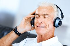 Handsome gray haired senior man with headphones. Listening to music in the living room royalty free stock photos