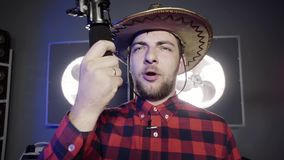 Handsome grey eyed bearded guy wearing mexican hat holds microphone and sings. Handsome bearded grey eyed guy vlogger put on stylish mexican hat and red stock footage