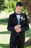 Handsome groom adjusting sleeve in garden. Handsome groom adjusting sleeve while standing in garden Royalty Free Stock Photography