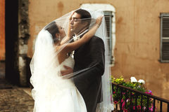 Handsome groom and beautiful bride kissing under veil in old eur Royalty Free Stock Photos