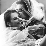 Handsome groom and beautiful bride kissing under veil in old str Stock Images