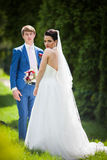 Handsome groom and beautiful bride posing in park, trees backgro Royalty Free Stock Image