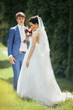 Handsome groom and beautiful bride posing in park, trees backgro Stock Photo
