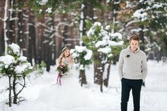 Handsome groom in beige pullover on background of blurred bride in snowy forest. Winter wedding. Artwork. stock images