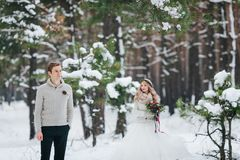 Handsome groom in beige pullover on background of blurred bride in snowy forest. Winter wedding. Artwork. royalty free stock photo