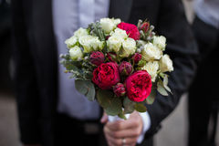 Handsome groom in black suit holding wedding bouquet Royalty Free Stock Photo