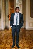 Handsome groom in black suit posing. Luxurious hotel room background Stock Image