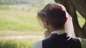 Groom comes to charming blonde bride with bouquet behind her. Slow motion. Handsome groom comes to charming blonde bride with bouquet behind her, outdoors. Slow stock video