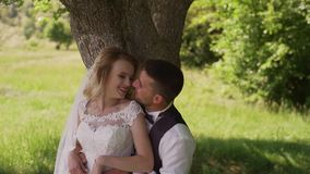 Groom comes to charming blonde bride with bouquet behind her. Slow motion. Handsome groom comes to charming blonde bride with bouquet behind her, outdoors. Slow stock footage
