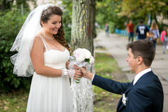 Handsome groom giving bouquet to smiling bride at park Royalty Free Stock Photo