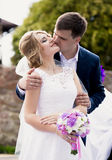 Handsome groom giving a kiss on brides cheek Stock Images