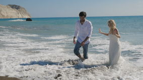 Handsome groom go on the shore from ocean and bride stands in the water stock footage