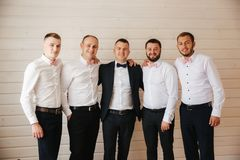 Handsome groom with his groomsman at home. Five man. Groom dressed in suit, gromsmen in white shirt. Funny guys on the. Wedding stock photo