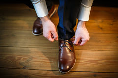 Handsome groom on his wedding day. Tying a shoe lace Stock Photos