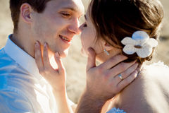 Handsome groom holds in hands beautiful bride's face close up Stock Images