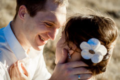 Handsome groom holds in hands beautiful bride's face close up Royalty Free Stock Images