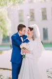 Handsome groom holds in hands beautiful bride's face close up outdoors Stock Image