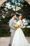 Handsome groom hugging beautiful bride with bouquet in romantic european park Royalty Free Stock Images