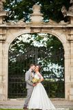 Handsome groom hugging beautiful bride with bouquet in romantic european park Royalty Free Stock Photography
