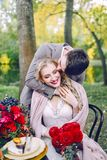 The handsome groom hugging his bride at the festive table. Autumn wedding. Artwork Royalty Free Stock Images