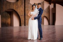 Handsome groom hugging his young and beautiful bride stock photography