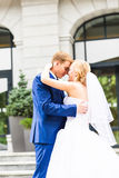 Handsome groom kissing beautiful bride outdoors. Handsome groom kissing beautiful young bride outdoors stock photography