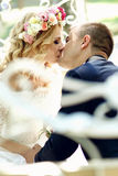 Handsome groom kissing blonde beautiful bride in magical fairy t. Ale carriage close-up Stock Image
