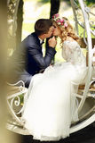 Handsome groom kissing blonde beautiful bride in magical fairy t. Ale carriage close-up Stock Photography