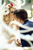 Handsome groom kissing blonde beautiful bride in magical fairy t. Ale carriage close-up Stock Photos