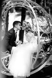 Handsome groom kissing blonde beautiful bride in magical fairy t. Ale carriage close-up b&w Stock Images