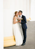 Handsome groom kissing cheerful bride in cheek Royalty Free Stock Image