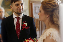 Handsome groom looking at beautiful bride, happy groom in stylis Royalty Free Stock Photography