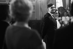 Handsome groom looking at beautiful bride, happy groom in stylis Stock Images