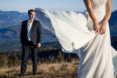 Handsome groom looking at his beatiful bride posing on foreground. Honeymoon in the mountains Stock Photography