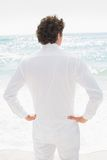 Handsome groom looking out to sea with hands on hips Royalty Free Stock Photo
