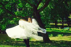 Handsome groom man circling bride. Handsome groom men circling with beautiful bride women in wedding veil in hair and white flying dress on hands outdoors in stock photos