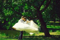 Handsome groom man circling bride. Handsome groom men circling with beautiful bride women in wedding veil in hair and white flying dress on hands outdoors in stock photography