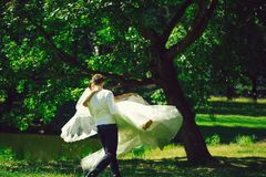 Handsome groom man circling bride. Handsome groom men circling with beautiful bride women in wedding veil in hair and white flying dress on hands outdoors in stock photo