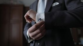 Handsome groom man fixes his cuffs on a jacket with cufflinks. Businessman